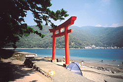 A torii gate stands beside the beach at the harbor in Heda
